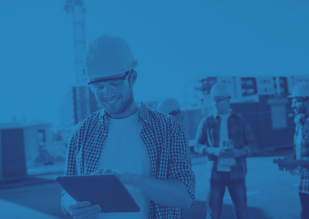 Man on a construction site wearing a hard hat and protective glasses. He is smiling and looking at a tablet device. There are containers and workers in the background, out of focus. There is a blue filter on the image.